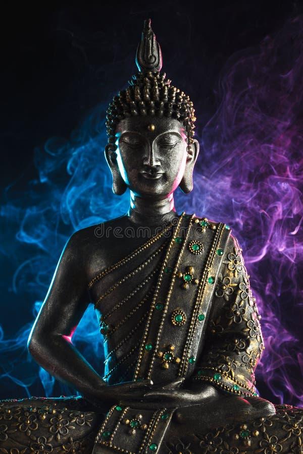 Statua di Buddha con fumo colorato immagini stock