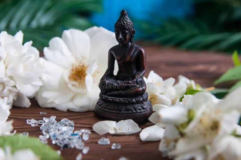 Statua di Buddha con i fiori bianchi, foglie verdi su fondo di legno Concetto di armonia, di equilibrio e della meditazione, fotografie stock libere da diritti