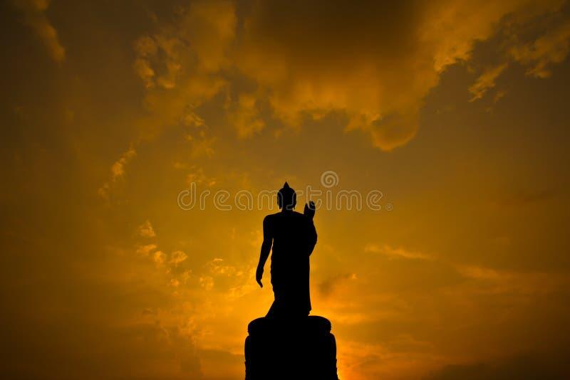 Statua di Buddha della siluetta nel tramonto fotografia stock
