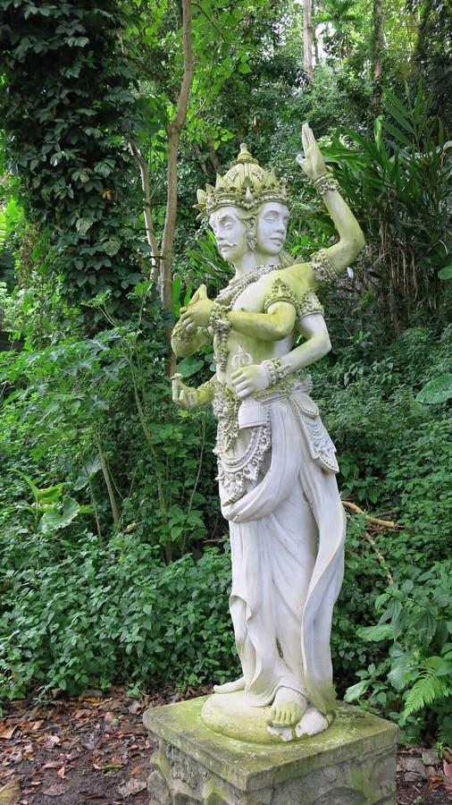Statua di Dio indù sull'isola di Bali Dio indù nel giardino reale di Tirta Gannga Una statua su un piedistallo di pietra bianco fotografia stock libera da diritti
