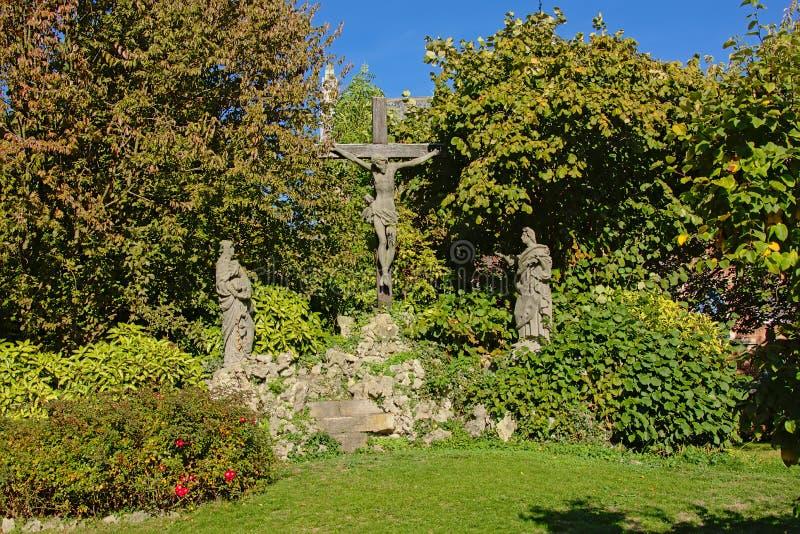 Statua di Gesù sull'incrocio con Maria e Mary Magadelen che si inginocchiano accanto  immagine stock libera da diritti