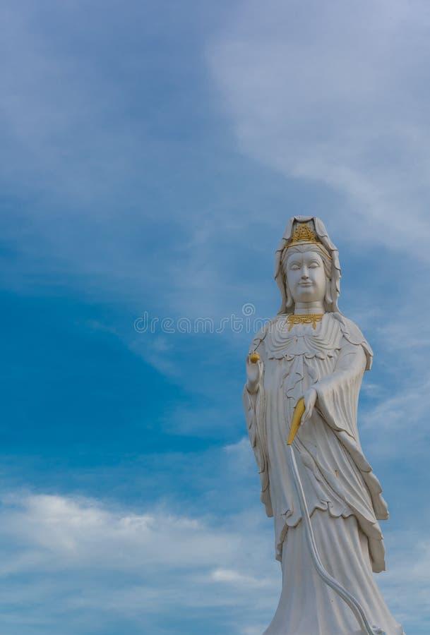 Statua di Guanyin Buddha su cielo blu fotografie stock libere da diritti
