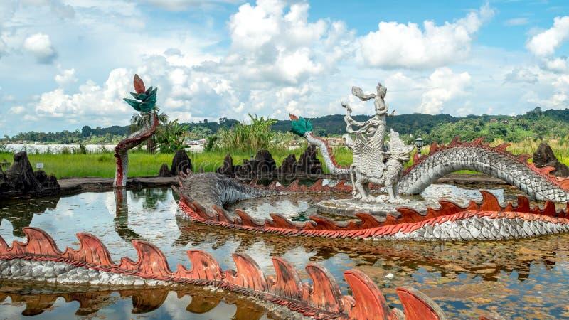 Statua di Lembuswana circondata con la figura del drago nello stagno con il bello cielo in Pulau Kumala, Indonesia immagine stock libera da diritti