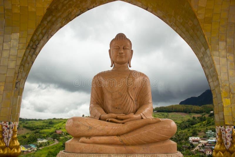 Statua di marmo arancio di Buddha nella posa di meditazione con il cielo luminoso i immagini stock