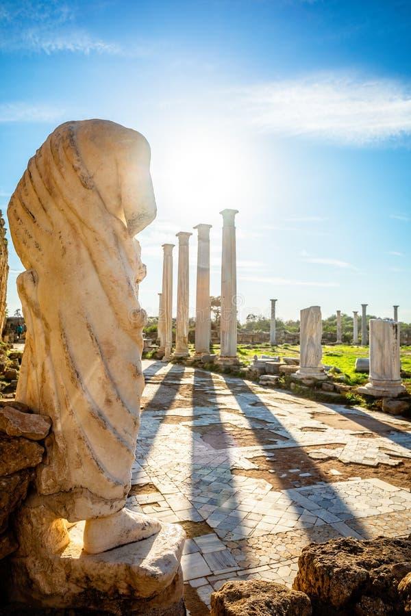 Statua di marmo sotto i raggi solari e colonne antiche a Salamis, sito archeologico greco-romano di Famagosta, Cipro settentriona fotografia stock