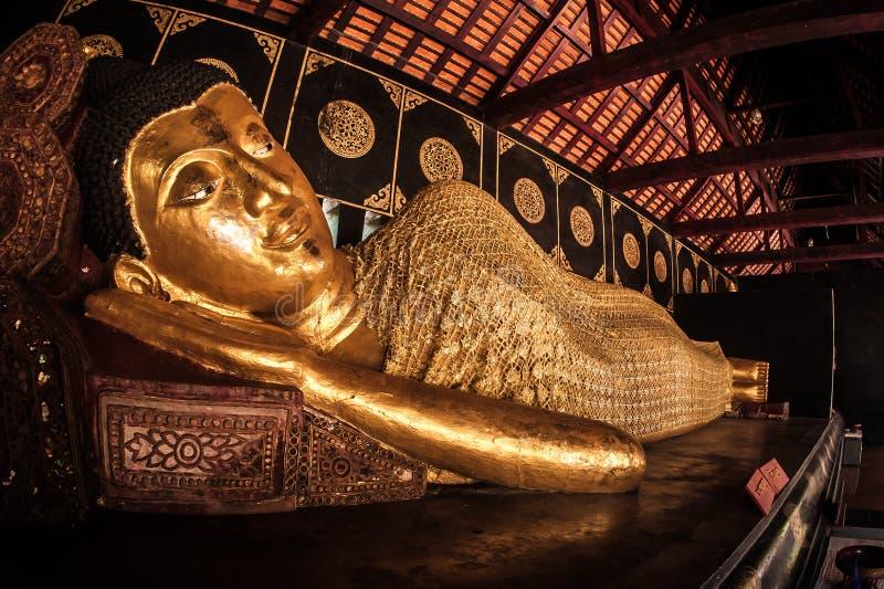 Statua di menzogne adagiantesi di Buddha al tempio buddista in Tailandia fotografia stock libera da diritti