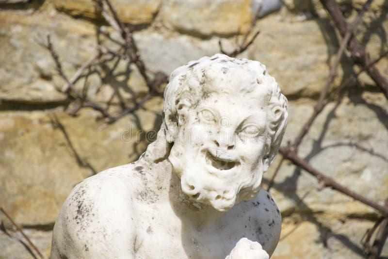 Statua di pietra all'aperto dell'uomo anziano divertente fotografie stock