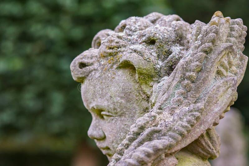 Statua di pietra di angelo in giardino Statua di angelo custode al sole come simbolo di amore in giardino immagine stock libera da diritti