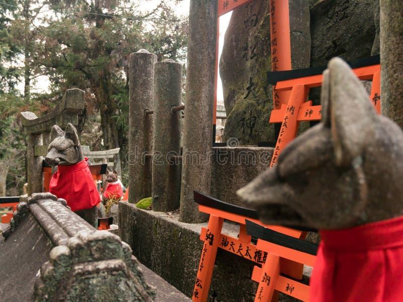 Statua di pietra delle volpi al santuario di Fushimi Inari nel Giappone fotografia stock
