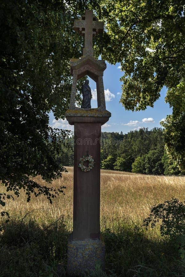Statua di pietra di tortura divina fra gli alberi su un percorso del campo fotografie stock
