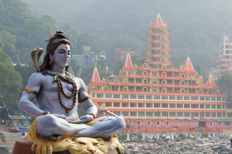Statua di Shiva che si siede nella meditazione sulla riva di Ganga in Rishikesh, Tera Manzil Temple, Trayambakeshwar nel fondo immagine stock
