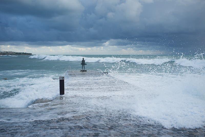 Statua di un giovane pescatore nelle onde fotografia stock