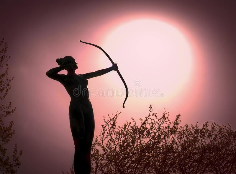 Statua di una donna Archer Silhouette con un obiettivo dell'arco il sole fotografia stock