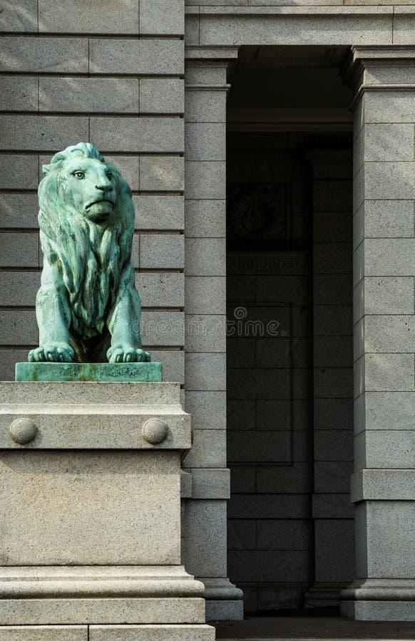 Statua di una guardia di condizione del leone davanti alla costruzione di mattone di pietra immagini stock
