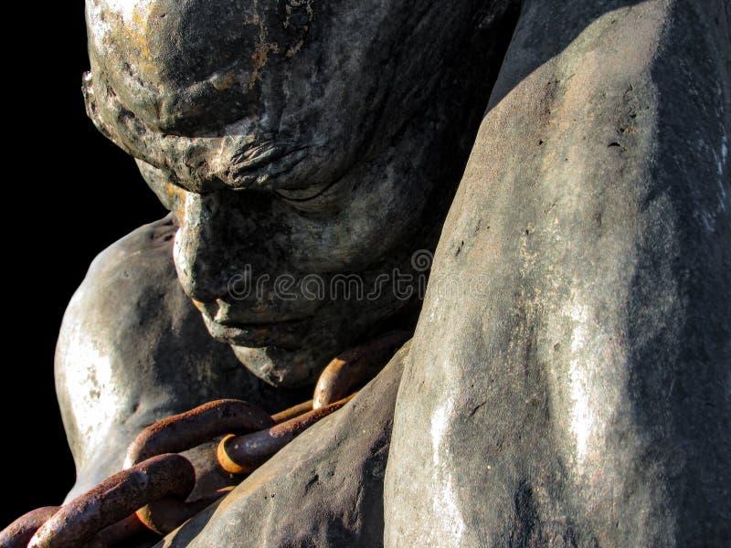 Statua di uno schiavo che porta una barca facendo uso di una catena fotografia stock libera da diritti