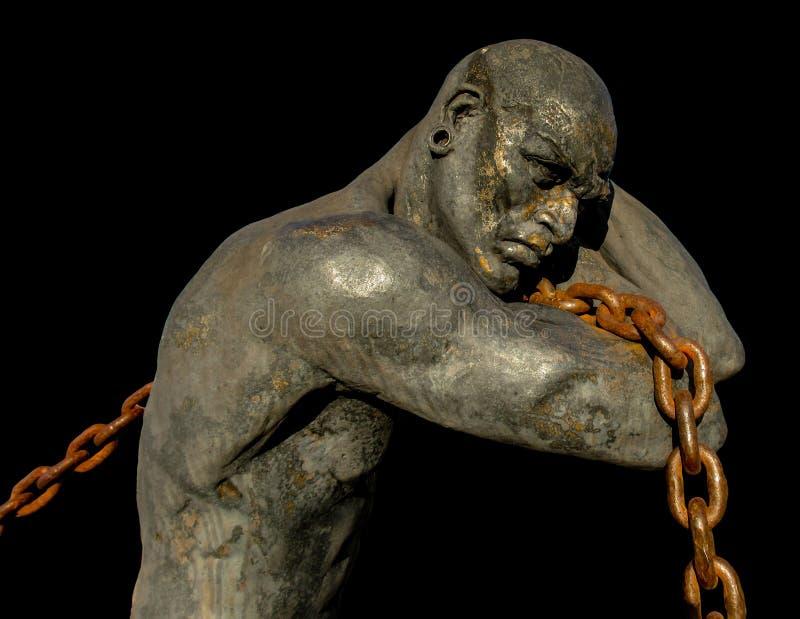 Statua di uno schiavo che porta una barca facendo uso di una catena fotografie stock libere da diritti