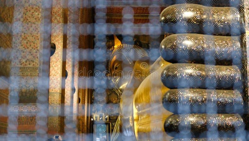 statua dorata adagiantesi di Buddha al pho del wat a Bangkok, Tailandia immagine stock