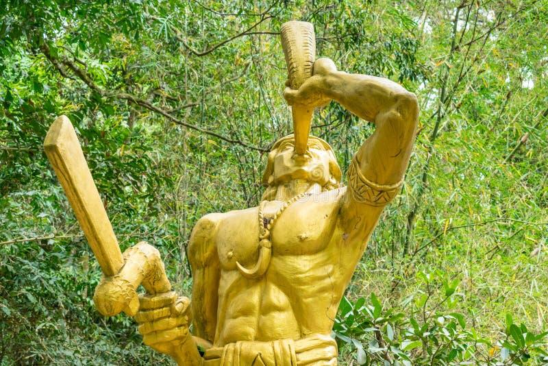 Statua dorata del guerriero con il corno e dell'amuleto nella forma della zanna fotografie stock libere da diritti
