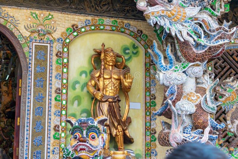 Statua dorata del guerriero in tempio variopinto nel Vietnam immagini stock libere da diritti