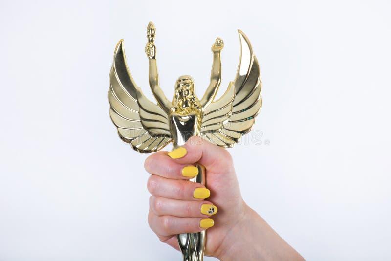 Statua dorata di angelo con la torcia ed ali aperte in mano femminile fotografia stock