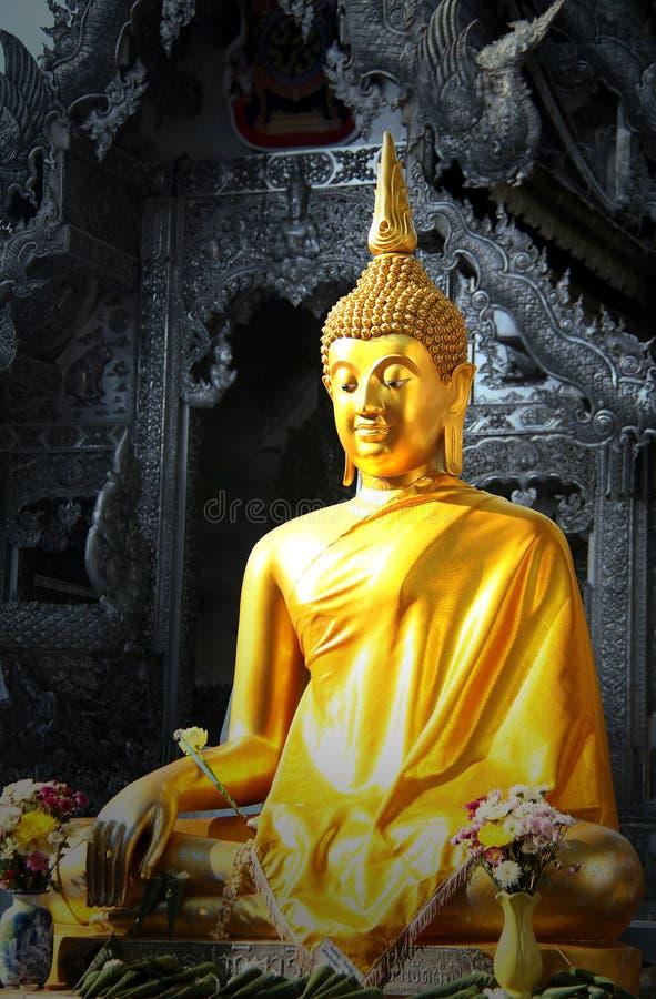 Statua dorata di Buddha davanti al tempio metallico immagini stock libere da diritti