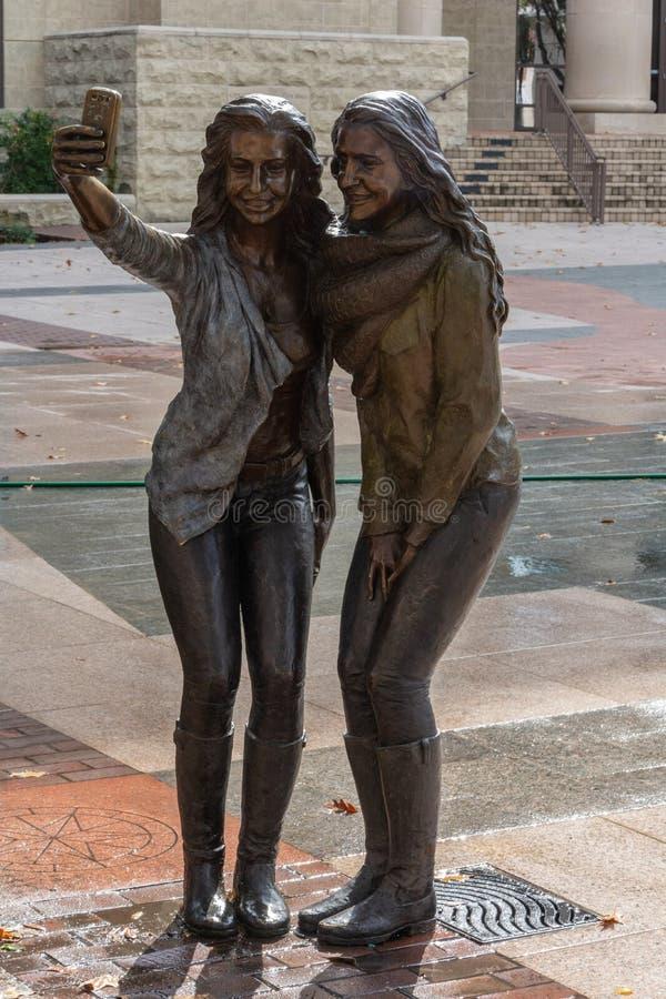 Statua dwa dziewczyny pozuje dla selfie fotografii w cukier ziemi, TX zdjęcia royalty free