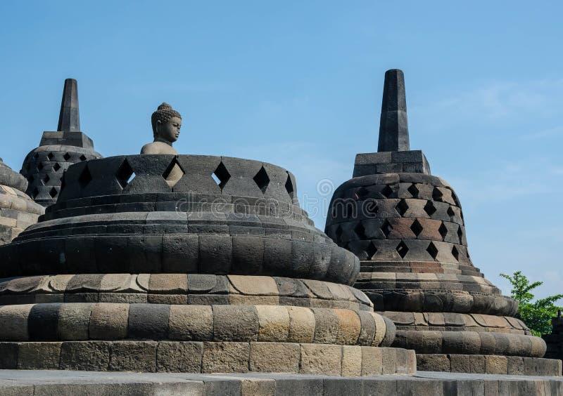 Statua e stupa antichi di Buddha al tempio di Borobudur in Yogyakart immagine stock