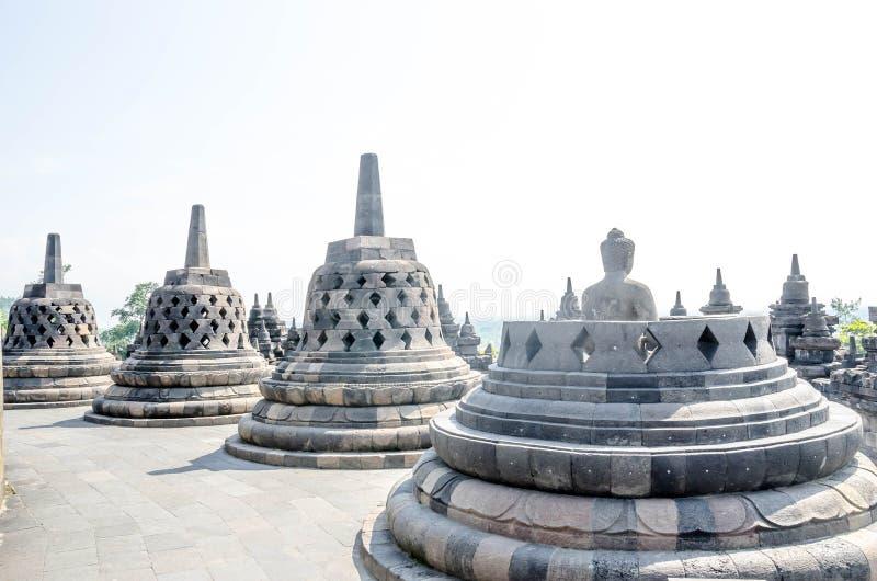 Statua e stupa antichi di Buddha al tempio di Borobudur in Yogyakart fotografia stock