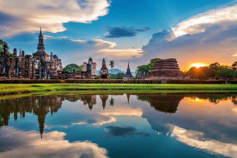 Statua e Wat Mahathat Temple di Buddha nel recinto del parco storico di Sukhothai fotografia stock libera da diritti
