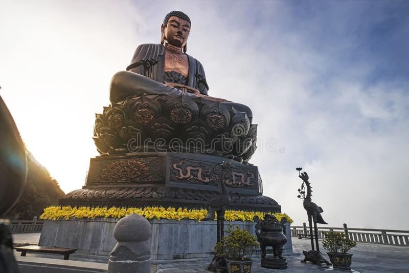 Statua gigante di Buddha sulla cima del cielo blu del picco di montagna di Fansipan, vista del contesto di bella e della nuvola i fotografia stock libera da diritti
