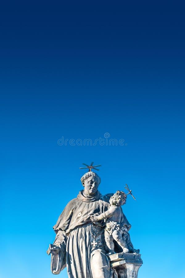 Statua gruby i du?y ksi?dz z dzieckiem przy Charles mostem w Praga przy niebieskim niebem, republika czech, lato czas fotografia royalty free