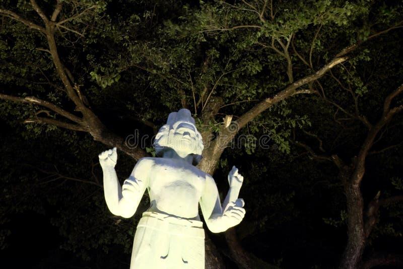 Statua Hinduski bóstwo z cztery rękami i kilka twarzami, nocy oświetlenie, Azjatycka kultura fotografia stock
