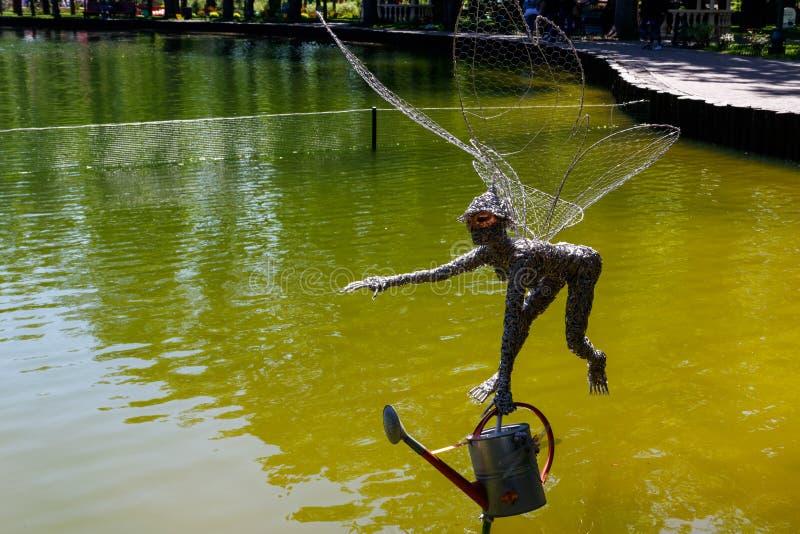 Statua latająca czarodziejka z podlewanie puszką nad jeziorem obrazy royalty free