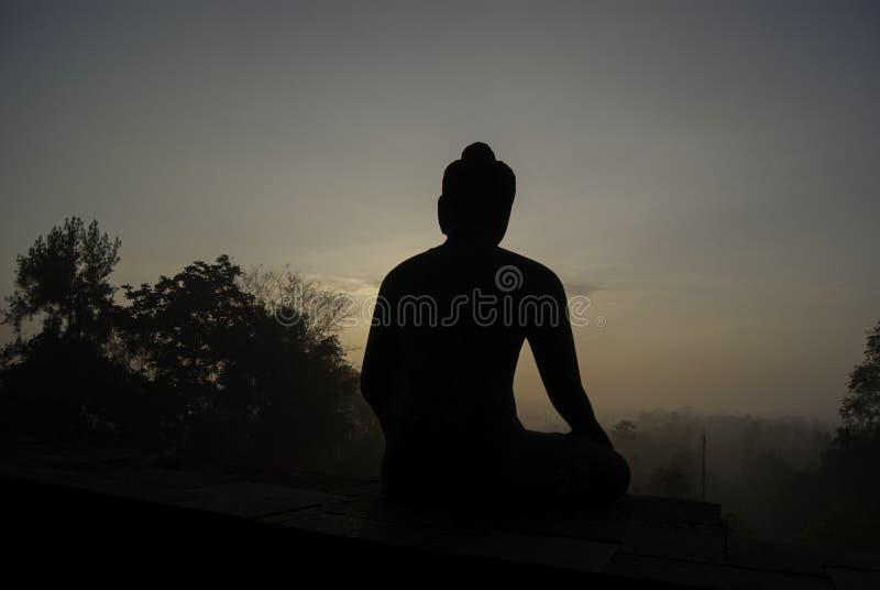 Statua messa di Buddha contro l'alba fotografia stock libera da diritti