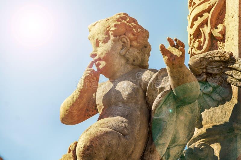 Statua robić kamień amorek, zabytek miłość, świecenie od słońca, Śmieszny z nadwagą amorka celowanie obraz royalty free