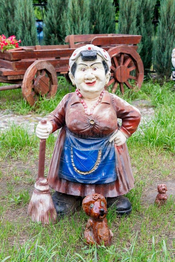 Statua stara kobieta z miotłą i psy ozdabiamy jarda obrazy royalty free