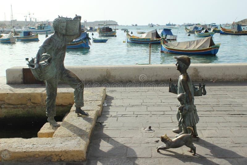 Statua tradizionale del bronzo di Marsaxlokk del paesino di pescatori immagine stock