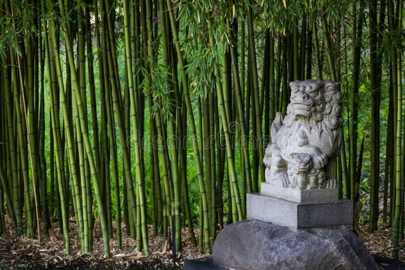 Statua tradizionale di Shisa o di Shi Shi Dog o Foo Dog - statua per evitare malvagità e da proteggere in un giardino di bambù fotografie stock