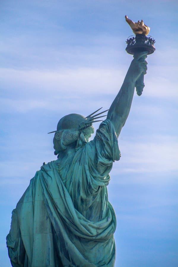 Statua Wolności kolosalna neoklasyczna miedziana rzeźba na swobody wyspie, Nowy Jork schronienie, NYC Tylny widok przeciw niebies obrazy royalty free