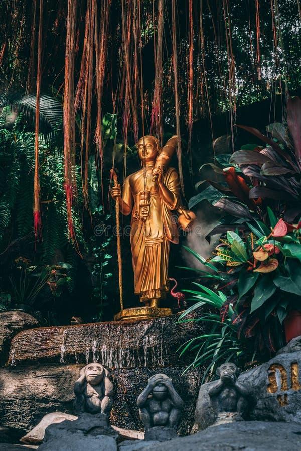 Statue à la montagne d'or à Bangkok 3 singes dans le premier plan et dans la statue d'or arrière entre le brouillard et le jardin photographie stock