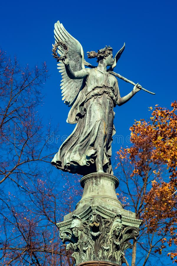 Statue of an angel on a column in bright sunshine. In autumn with clear blue skies royalty free stock images