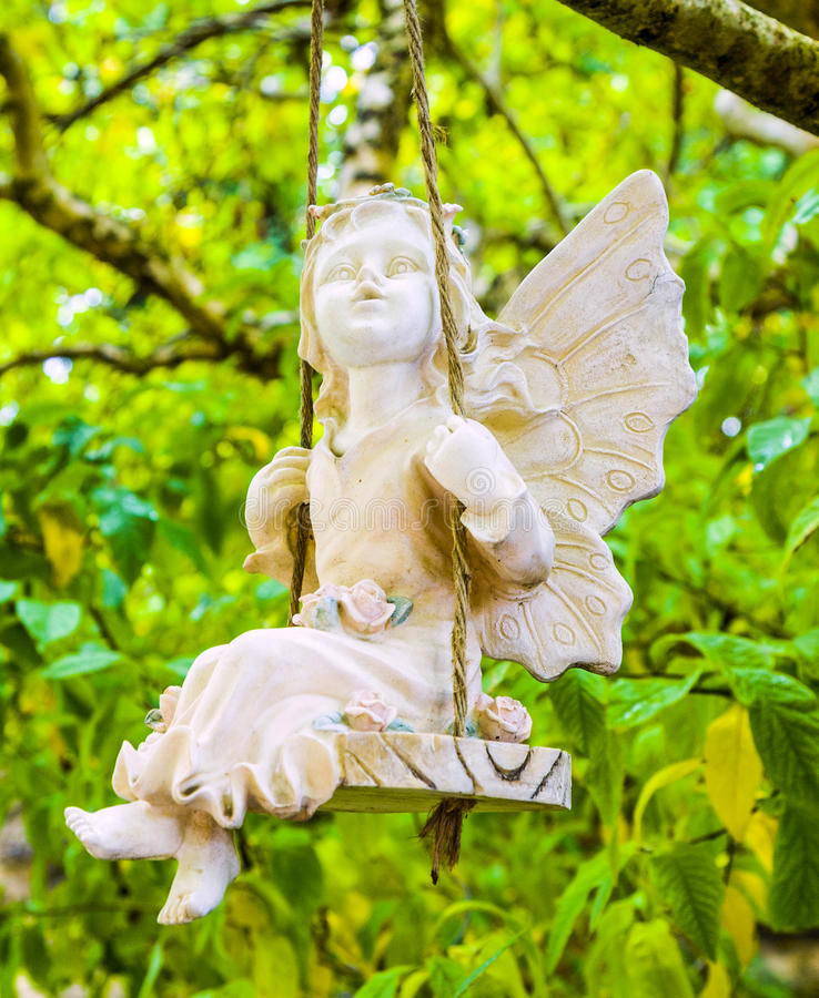 Statue of an angel sitting on a swing. In a tree stock photo