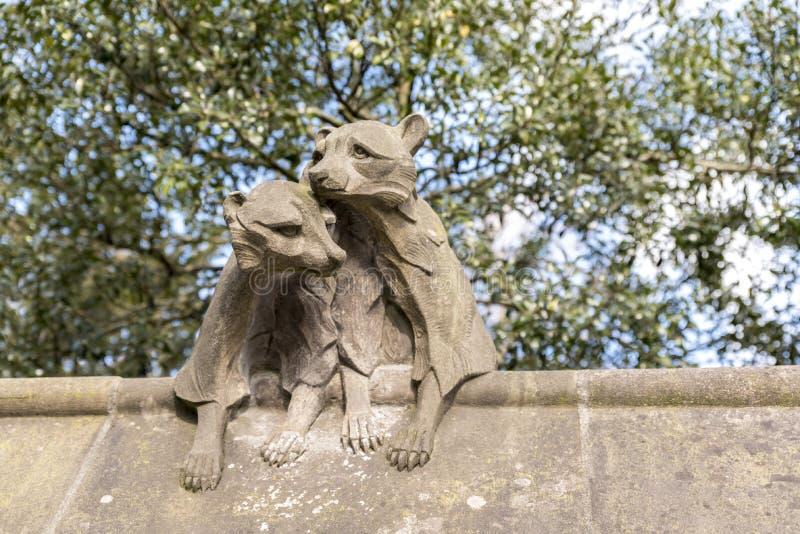 Statue animale en pierre donnant sur un mur photo stock
