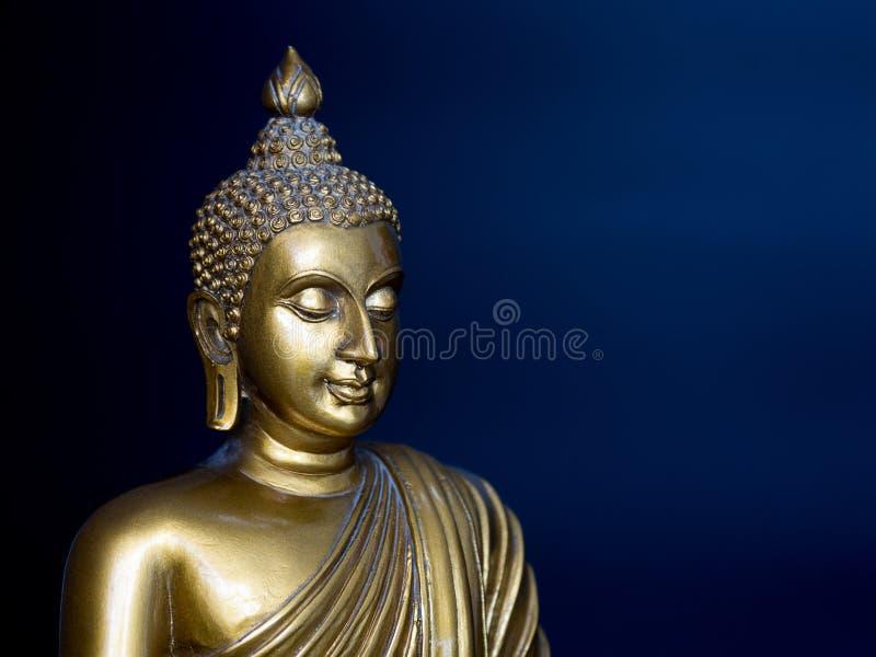 Statue antique d'or de Bouddha Le fond est bleu de minuit Le visage du Bouddha s'est tourné vers la gauche images stock