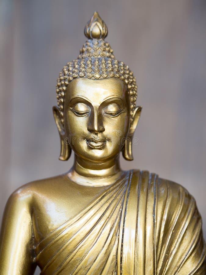 Statue antique d'or de Bouddha Le fond est gris d'ardoise léger Le visage du Bouddha s'est tourné vers le droit images stock