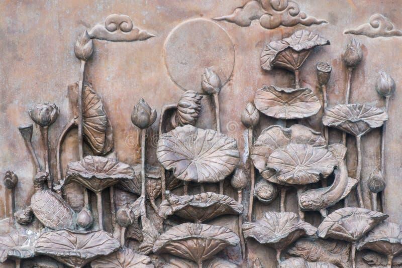 Statue antique de lotus sur le mur photo stock