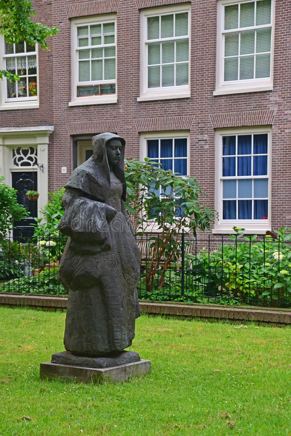 Statue of a Beguine in the beautiful courtyard of The Begijnhof at Amsterdam. The Netherlands. This statue is crafted in 1974 by Dutch sculptor Margaretha de stock images
