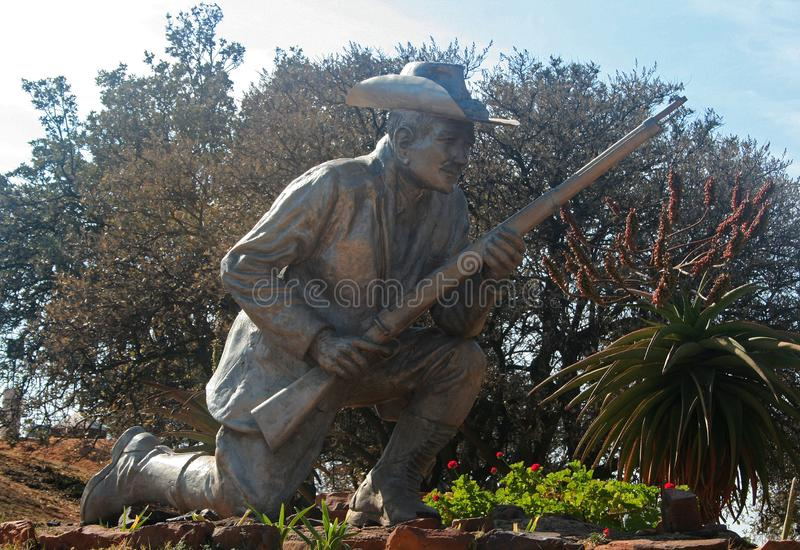 STATUE OF BOER PIONEER POSED IN AN OBSERVATION POST ROLE. View of a bronze statue of an Afrikaner pioneer kneeling down on one knee with his rifle poised stock photos