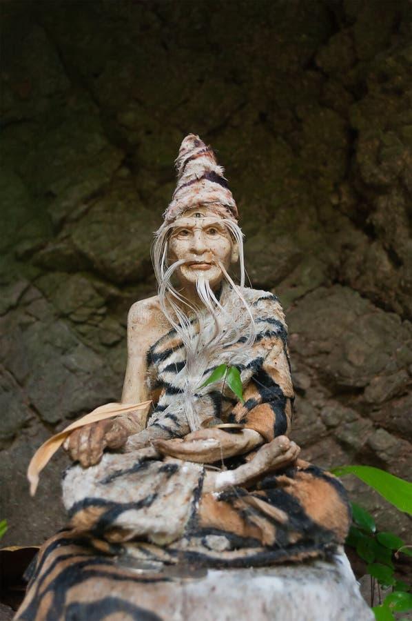 Statue bouddhiste avec un troisième oeil dans une roche dans la forêt antique photo stock