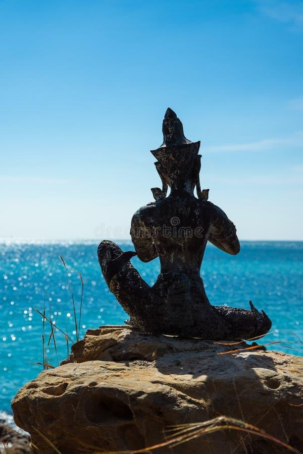 Statue bouddhiste sur la roche regardant la mer image stock